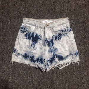 Distressed tie dye denim shorts